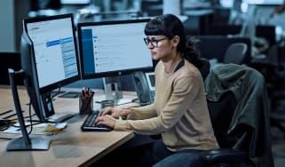 Woman typing at desk surrounded by three monitors