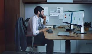 Man sat at desk looking at monitors
