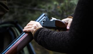 A person unloading a hunting shotgun