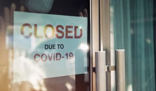 Unidentified person wearing mask hanging closed sign on front door