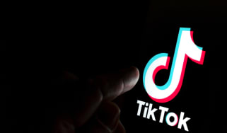 A finger about to press the TikTok logo in the dark