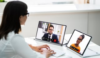 Woman sat at desk video conferencing on two screens