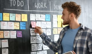 Scrum master in front of a board with jobs written on sticky notes