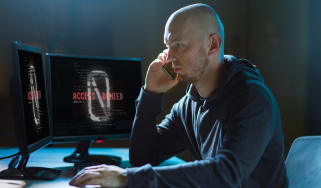 A fraudulent call centre agent in a dark room surrounded by monitors