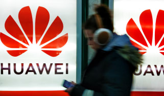 A shot of a woman walking in front of a Huawei sign
