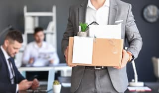 Man leaving a job with box of personal items