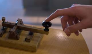 Finger pressing a Morse code receiver