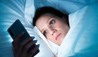 A women in bed checking her phone before going to sleeep