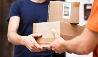 A person wearing an orange T-shirt is delivering parcels to a satisfied client