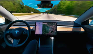 A Tesla Model 3 driving with the Autopilot