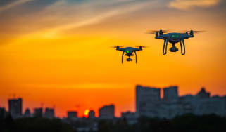 Two drones flying over a cityscape while the sun sets
