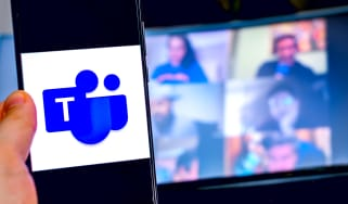 Hand holding a phone with Microsoft Teams app with video call in background