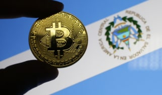 Fingers holding a 'bitcoin' in front of the flag for El Salvador