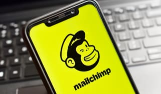 The Mailchimp logo on a smartphone in front of a keyboard
