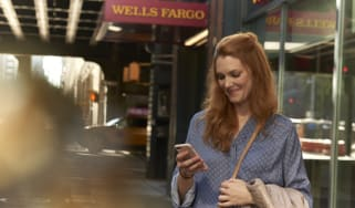 A woman looks at her phone with Wells Fargo sign in background