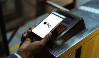 Close-up view of man using Apple Pay paying for public transport