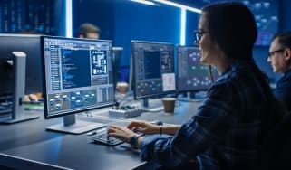 A cyber security professional at their desk in an office