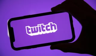 The Twitch logo on a smartphone being held by a shadowy hand