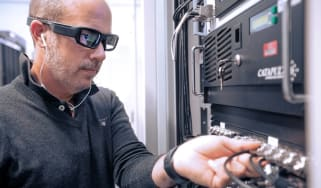 A Vodafone engineer is working on a server using Eyes in the Lab glasses