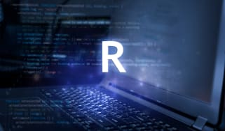 """""""R"""" over top of a laptop with code on it"""