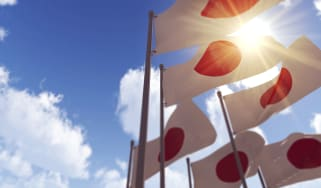 Japanese flags in front of a blue cloudy sky