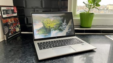 The HP EliteBook 840 G7 as seen from the front, with a cookbook and window in the background