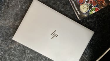 The lid of the HP EliteBook 840 G7 with HP logo and cookbook in background