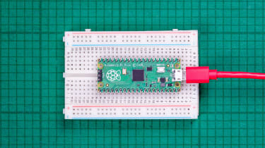 The Raspberry Pi Pico on a breadboard, connected with a red cable