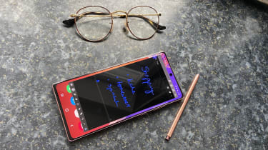 The Samsung Note 20 as seen from above with a shopping list open on it screen (handwritten with stylus), located on a kitchen counter with glasses placed just above