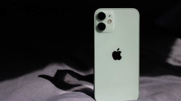 The Apple iPhone 12 mini standing up on a bed