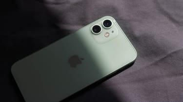 The Apple iPhone 12 mini face-down on a bed