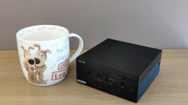 The Asus PN51 MiniPC on a desk next to a mug