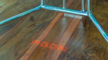 A photograph of the Agon logo projected from the Porsche Design AOC Agon PD27