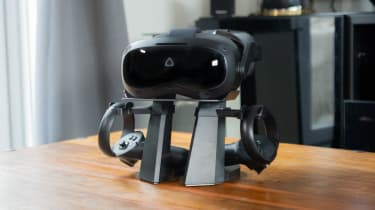 A photograph of the HTC Vive Focus 3 and its controllers, mounted on a stand on a coffee table