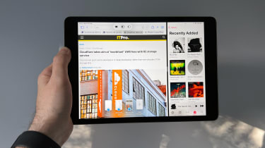 A photograph of the 12.9in 2021 Apple iPad Pro held in front of a wall
