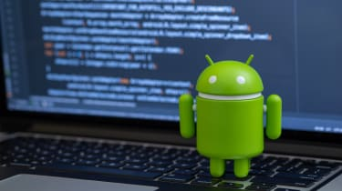 An Android figurine on a laptop with developer code on the display