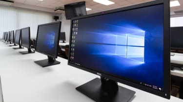 A long office desk with multiple PCs displaying Windows 10 home screen