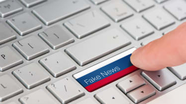 A finger pressing a 'Fake News' keyboard button with a Russian flag background
