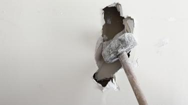 A sledgehammer smashing through a white wall