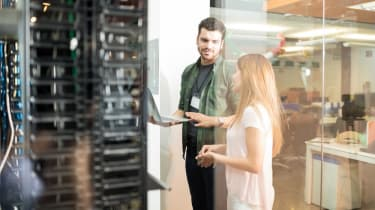 Two co-workers near a set of servers