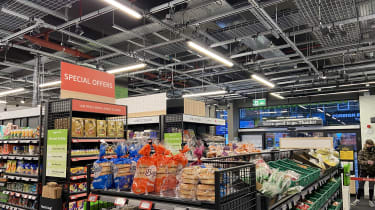 A photo of the black boxes that monitor customers in the Amazon Fresh shop hanging from the ceiling with shelves in the foreground and the exit in the background