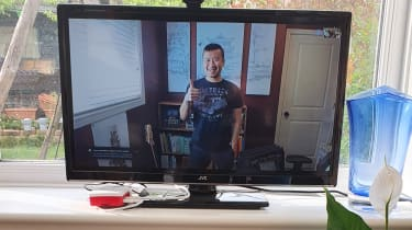 A smiling person on a TV screen showing thumbs up