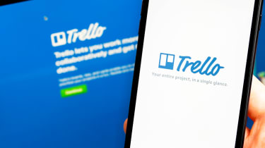 Hand holding a phone that says Trello with same welcome page on laptop in background