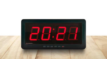 A digital clock displaying 8:21 pm in red led light, on brown wooden table on white background