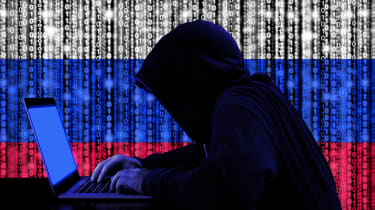 Abstract silhouette of a computer hacker in front of a Russian flag