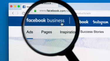 A magnifying glass examining a Facebook page
