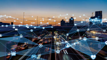 A city skyline at dusk overlaid with graphics to show an IoT network