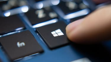 A finger about to push the windows button on a laptop keyboard
