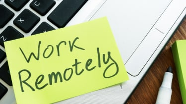 """""""Work Remotely"""" post-it note stuck to a laptop"""