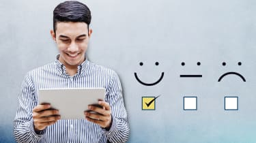 A man looks at his tablet with a happy expression